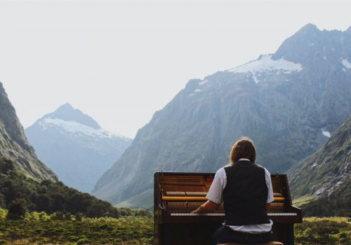A student playing piano in front of mountains in New Zealand